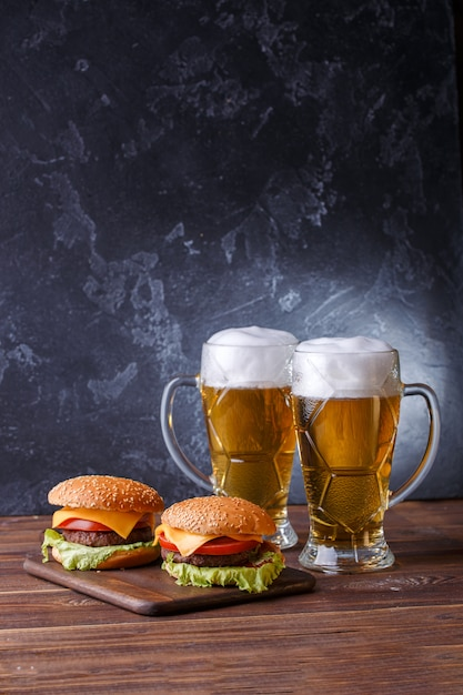 Photo de deux hamburgers, verres à bière Photo Premium