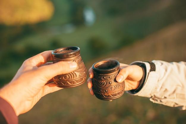 Photo De Deux Mains Tenant Deux Tasses De Boisson Chaude Dans La Nature Le Matin Photo Premium