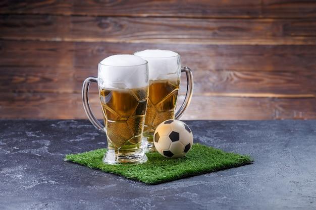 Photo de deux verres de bière, ballon de foot sur l'herbe verte Photo Premium