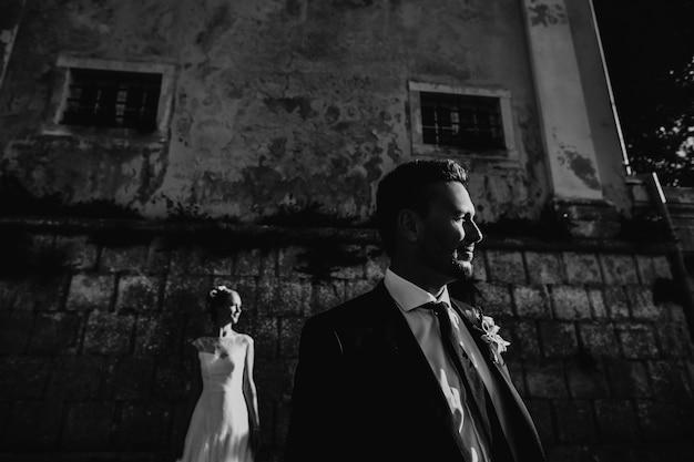 Photo dramatique en noir et blanc d'un couple de mariage posant devant un mur de pierre Photo gratuit