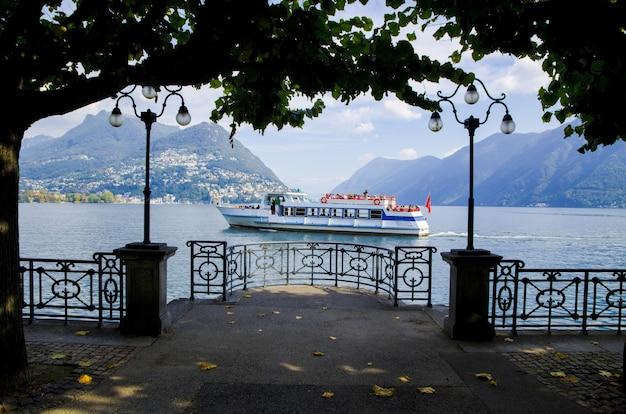 Photo Fascinante D'un Voilier Contre Les Montagnes Brumeuses à Lugano, Suisse Photo gratuit