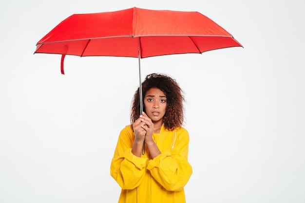 Photo De Femme Africaine Confuse En Imperméable Se Cachant Sous Un Parapluie Sur Blanc Photo gratuit
