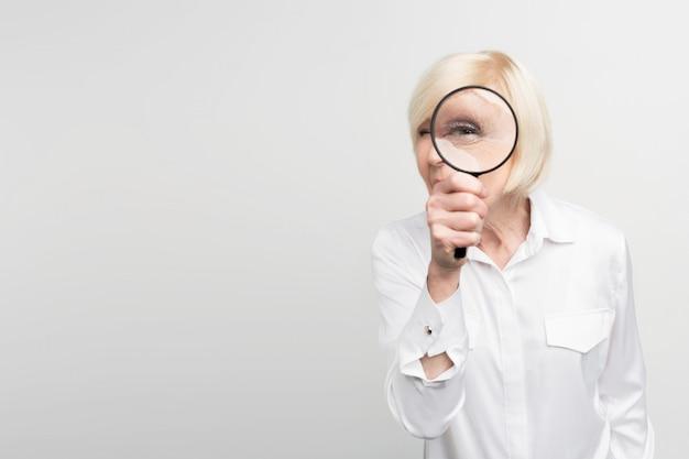 Une Photo D'une Femme Aux Cheveux Blancs Debout Sur Le Côté Droit Du Cadre Et Regardant Droit Devant La Loupe. Photo Premium