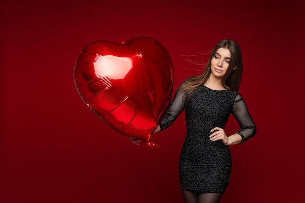 Photo D'une Femme Caucasienne Attrayante En Robe Noire Avec Ballon Coeur Dans Sa Main Sourit Sur Rouge Photo Premium