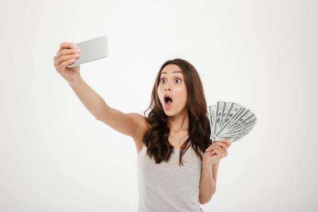 Photo De Femme Drôle Choquée Faisant Selfie Photographier Sur Mobile Argenté, Téléphone Tout En Tenant Fan De Billets D'un Dollar Isolé Sur Mur Blanc Photo gratuit
