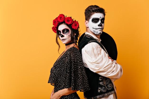 Photo De Fier Couple Mexicain En Vêtements Traditionnels Avec Des Visages Peints. Fille Avec Des Roses Dans Ses Cheveux Pose Avec Un Jeune Homme Avec Un Sombrero Dans Le Dos. Photo gratuit