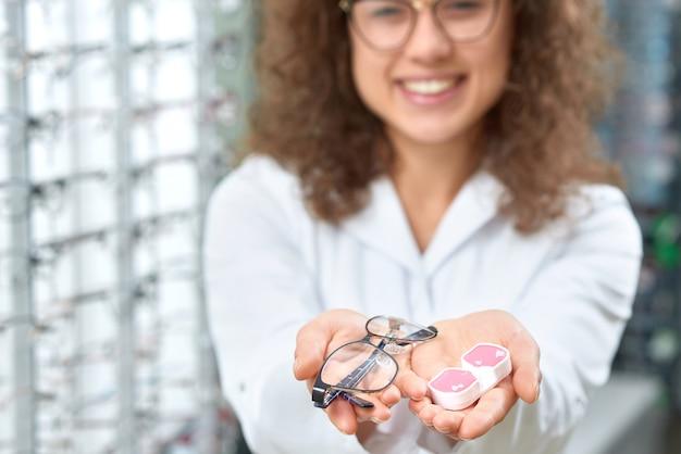 Photo floue d'un oculiste souriant aidant à choisir des lunettes. Photo Premium