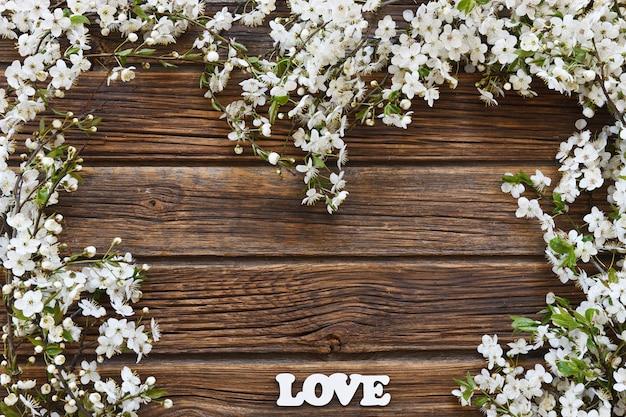 Photo en gros plan de belles branches blanches de cerisier en fleurs avec des lettres blanches d'amour. Photo Premium