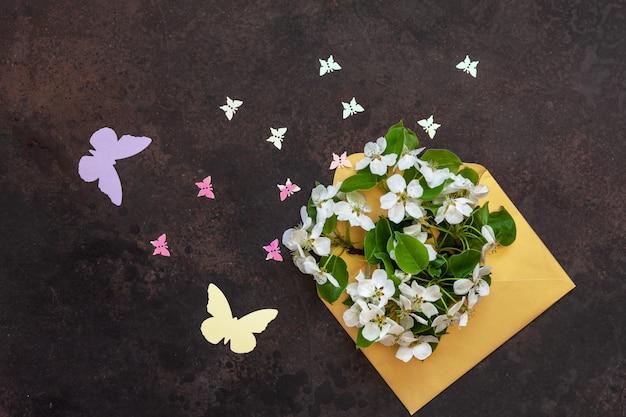 Photo en gros plan de belles branches de cerisier en fleurs blanches dans une enveloppe dorée avec des figurines de petits papillons. vue de dessus, carte de félicitations. Photo Premium