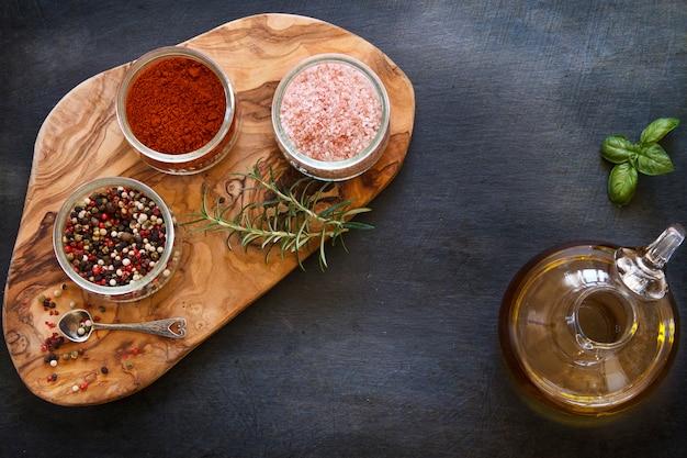 Photo en gros plan d'épices séchées colorées dans des bols sur une planche en bois sur une table bétonnée noire avec de l'huile d'olive dans un bocal Photo Premium
