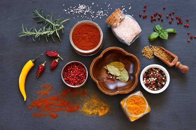 Photo en gros plan d'épices séchées colorées sur une table bétonnée noire Photo Premium