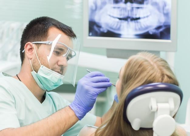 Photo En Gros Plan D'une Jeune Femme Assise Sur La Chaise Du Dentiste Avec La Bouche Ouverte Au Bureau Du Dentiste Pendant L'examen. Photo Premium