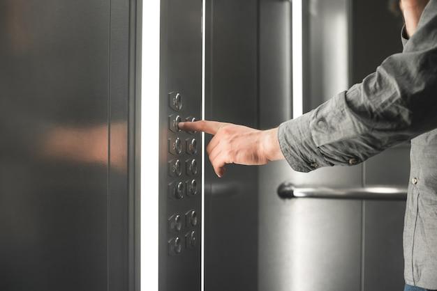 Photo En Gros Plan D'une Main Choisit Un étage Dans L'ascenseur. Photo Premium