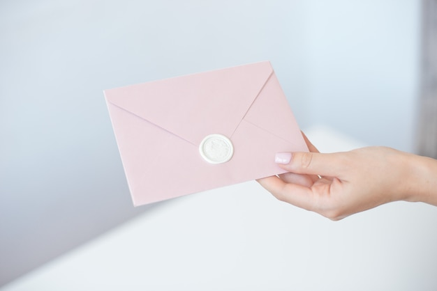 Photo En Gros Plan De Mains Féminines Tenant Une Enveloppe D'invitation Avec Un Sceau De Cire, Un Chèque-cadeau, Une Carte Postale, Une Carte D'invitation De Mariage. Photo Premium