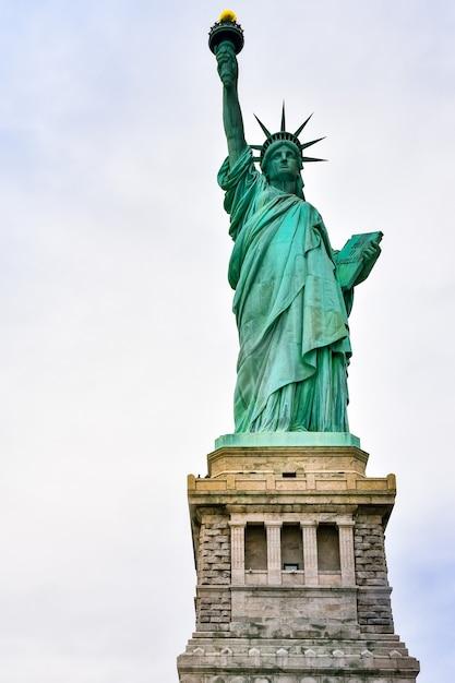 Photo Gros Plan De La Statue De La Liberté Par Une Journée Ensoleillée Et Ciel Bleu Avec Des Nuages. île De La Liberté. Nyc, états-unis. Photo Premium