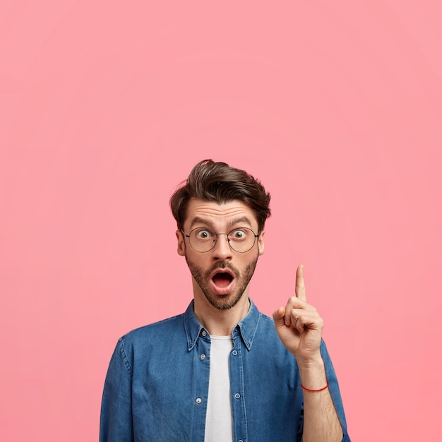 Photo D'un Homme De Race Blanche Stupéfié Avec Du Chaume Sombre, Garde La Bouche Largement Ouverte, Pointe Vers Le Haut Avec L'index, Vêtu De Vêtements à La Mode, Indique Un Espace Vide Vers Le Haut Contre Le Mur Rose Photo gratuit