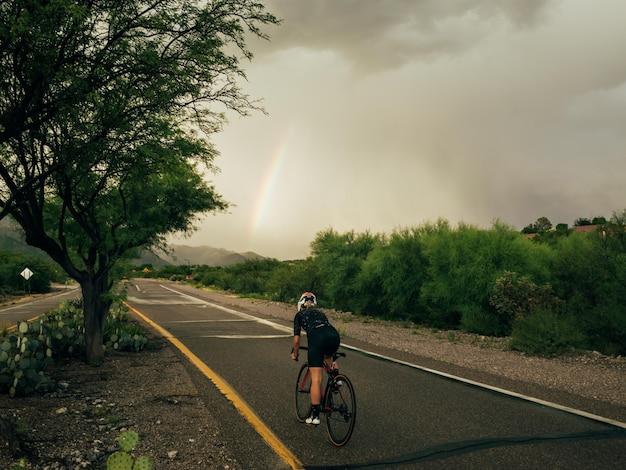 Photo Horizontale D'une Cycliste En Mouvement Qui Fait Du Vélo Sur La Route Sur La Nature Photo gratuit