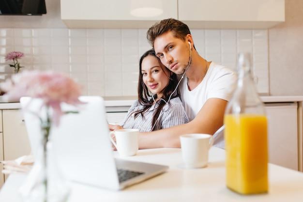 Photo Intérieure D'un Couple Aimant à L'aide D'un Ordinateur Portable, Tout En Se Détendant Dans La Cuisine Photo gratuit