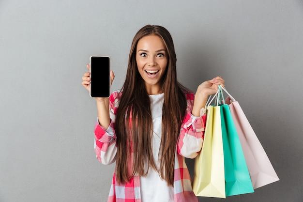 Photo D'une Jeune Brune étonnée Tenant Des Sacs à Provisions, Montrant Un écran Mobile Photo gratuit
