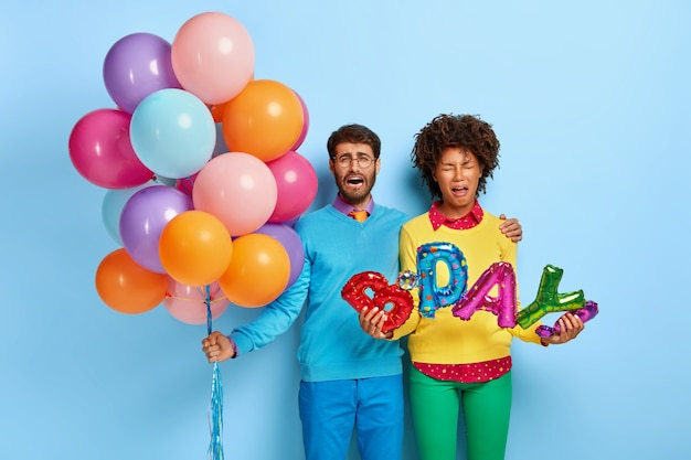 Photo D'un Jeune Couple Mécontent Lors D'une Fête Posant Avec Des Ballons Photo gratuit