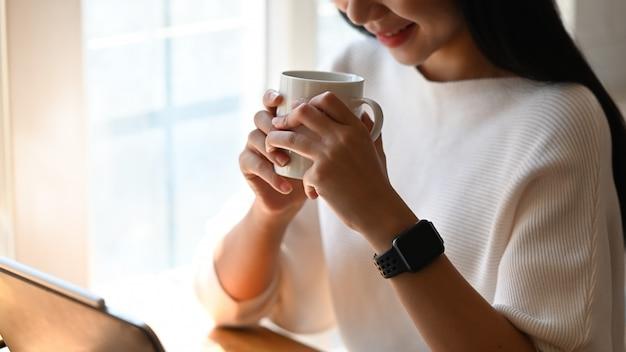 Photo D'une Jeune Femme Designer Tenant Une Tasse De Café Dans Ses Mains Alors Qu'elle était Assise à La Table De Travail Moderne Après Avoir Fini De Concevoir Un Nouveau Projet. Concept De Détente / Pause Après Le Travail. Photo Premium