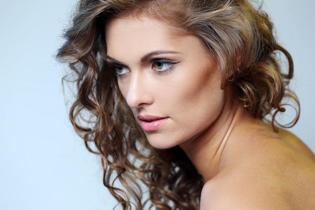 Photo de jeune fille brune avec une peau parfaite sur fond gris Photo gratuit