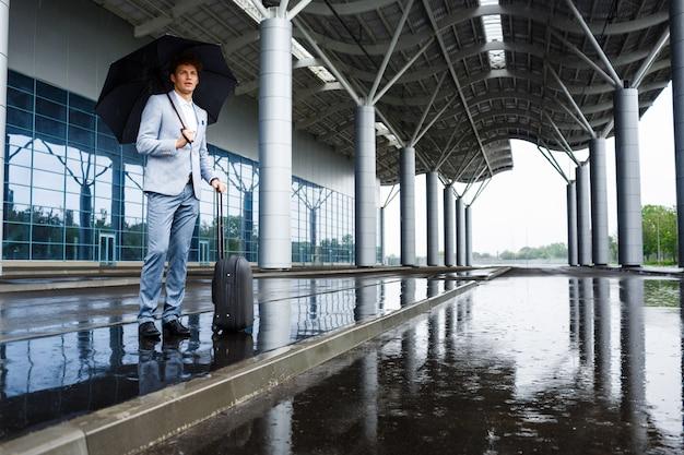 Photo De Jeune Homme D'affaires Aux Cheveux Roux Tenant Un Parapluie Noir Sous La Pluie Au Terminal Photo gratuit