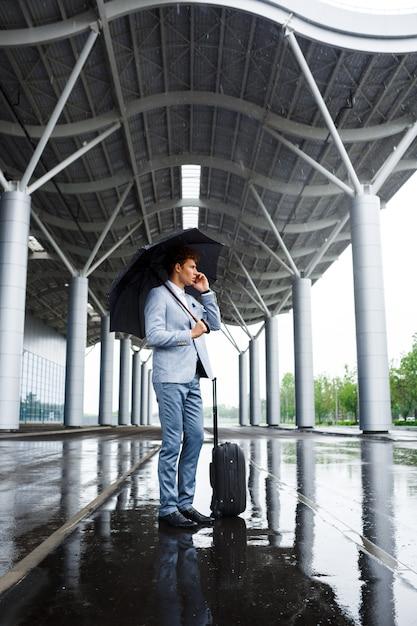 Photo De Jeune Homme D'affaires Aux Cheveux Roux Tenant Un Parapluie Noir Sous La Pluie Et Parler Au Téléphone Photo gratuit
