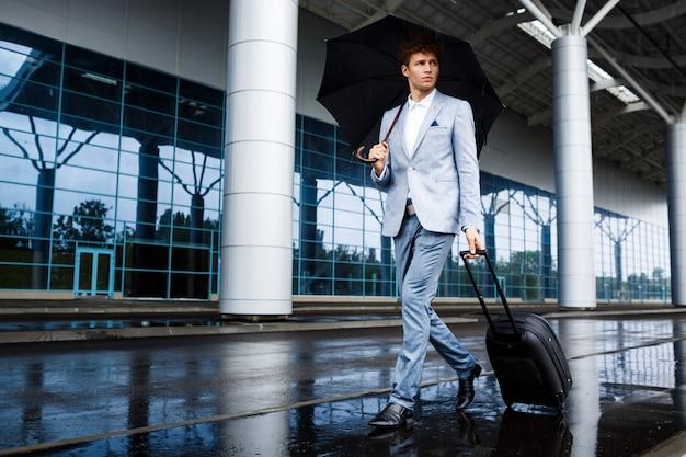 Photo De Jeune Homme D'affaires Aux Cheveux Roux Tenant Un Parapluie Noir Et Une Valise Marchant Sous La Pluie à L'aéroport Photo gratuit
