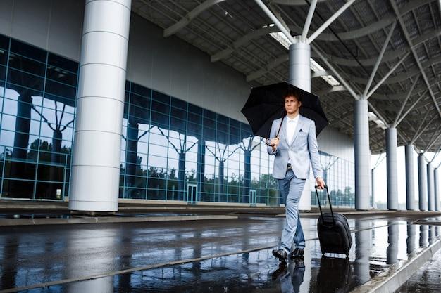Photo De Jeune Homme D'affaires Aux Cheveux Roux Tenant Un Parapluie Noir Et Une Valise Marchant Sous La Pluie à La Gare Photo gratuit