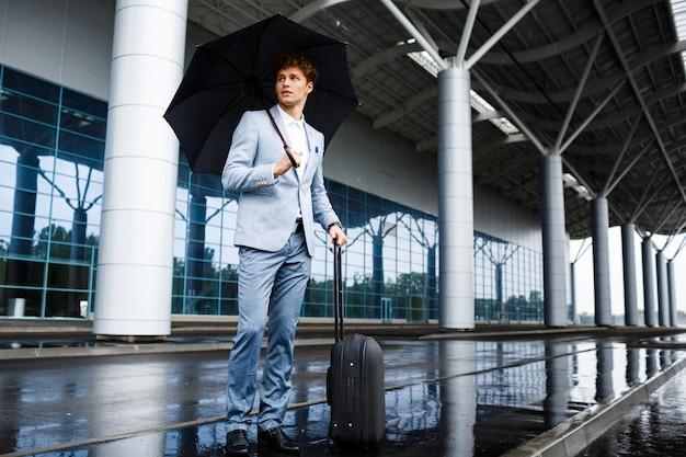 Photo De Jeune Homme D'affaires Aux Cheveux Roux Tenant Un Parapluie Noir Et Une Valise Sous La Pluie à L'aéroport Photo gratuit