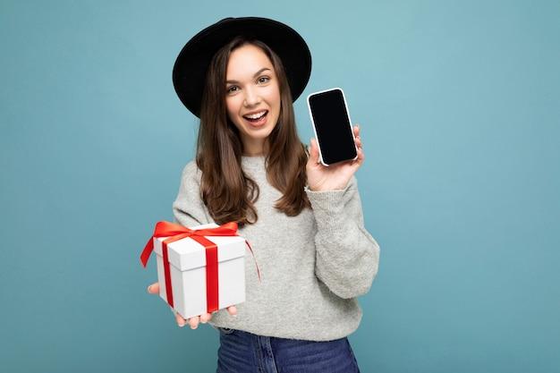 Photo De Jolie Jeune Femme Brune Positive Souriante Isolée Sur Fond Bleu Portant Un Mur Photo Premium