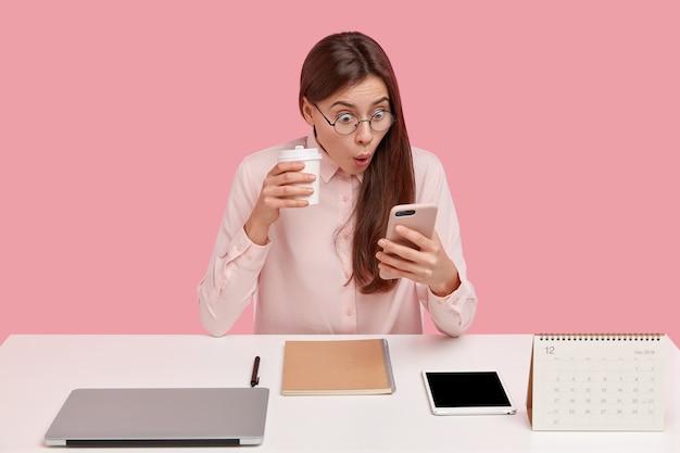 Photo De Jolie Jeune Femme Lit Des Nouvelles Choquantes Sur Téléphone Mobile, Regarde Des Vidéos Dans Les Réseaux Sociaux, Boit Du Café Dans Un Gobelet Jetable Photo gratuit