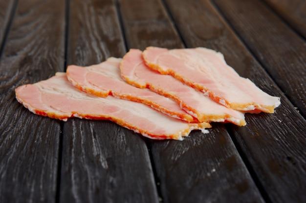 Photo à mise au point sélective de tranches de bacon frais sur une table en bois. Photo Premium