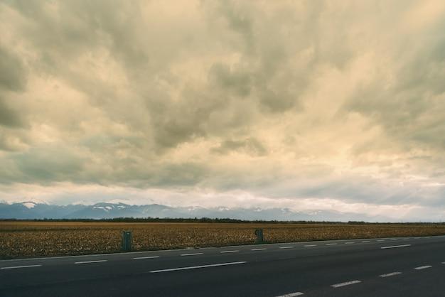 Photo De Paysage Avec Une Partie De La Route, Du Blé Et Des Montagnes Par Temps Nuageux. Photo Premium