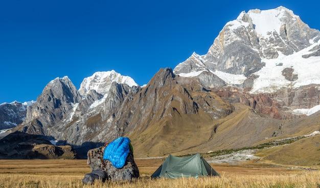 Photo De Paysage D'une Tente Verte Près D'un Rocher Dans Un Champ Entouré De Montagnes Couvertes De Neige Photo gratuit