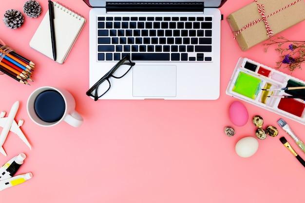 Photo plat plat de lieu de travail moderne avec ordinateur portable et des œufs, fond d'ordinateur portable vue de dessus et jeu de peinture préparant pâques sur fond rose Photo Premium