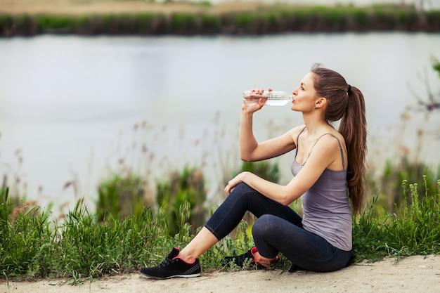 Photo en plein air d'une jolie jeune femme vêtue de vêtements de sport et d'eau potable assise au bord d'une rivière Photo Premium