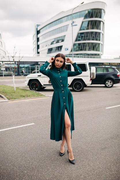 Photo Pleine Longueur De La Belle Jeune Femme Brune En Robe Verte Debout Dans La Rue Avec Un Bâtiment Moderne Sur Le Fond Photo gratuit