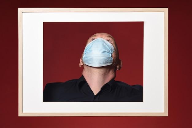 Photo D'un Portrait D'un Homme Avec Masque Regarder Sur Fond Rouge Photo Premium