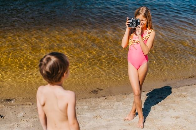 Photo prise de jeune fille de frère debout sur la plage de la mer Photo gratuit