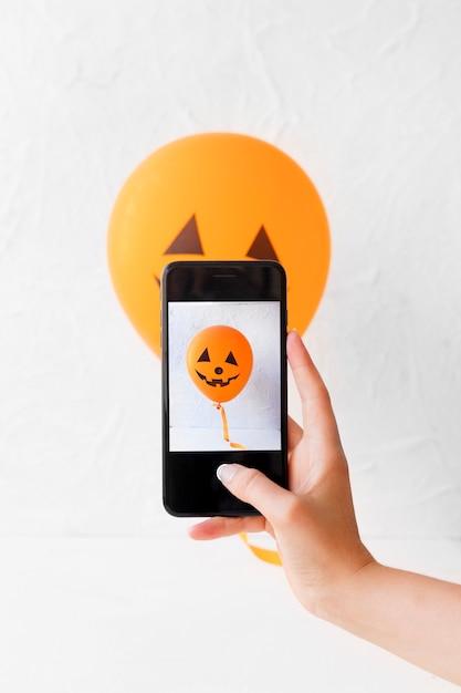 Photo de prise de main de culture du ballon de jack-o-lantern Photo gratuit