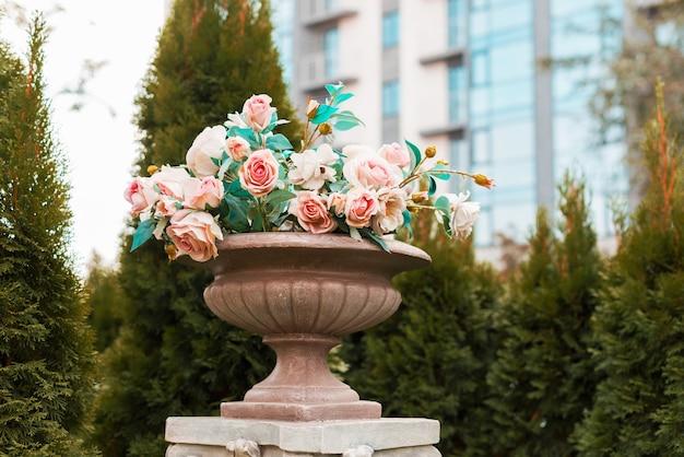 Photo De Quelques Belles Roses Roses Dans Un Vase En Pierre à L'extérieur Photo Premium