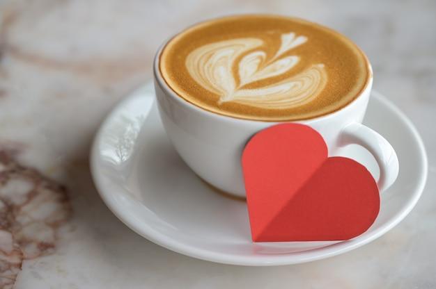 Photo Recadrée De Coeur De Papier Rouge Avec Texture De Coeur Café Latte Sur Plancher En Bois. Photo Premium