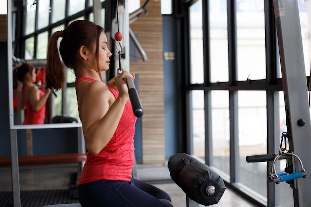 Photo recadrée de forte jeune femme tirant sur le matériel d'entraînement au gymnase. Photo Premium