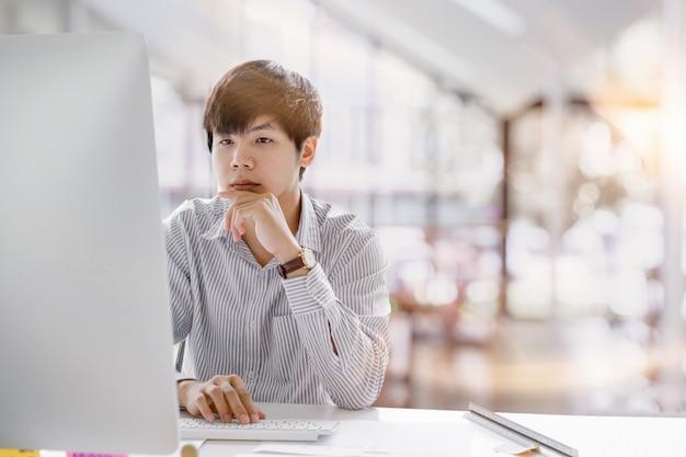 Photo recadrée d'un homme d'affaires asiatique sérieux pensant et se concentrant sur la saisie sur un ordinateur portable dans des espaces de travail en commun. concept de travail pour ordinateur portable homme Photo Premium