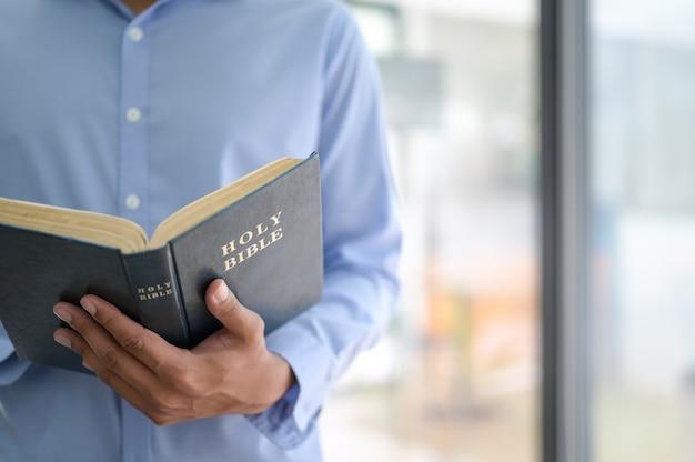 Photo Recadrée D'un Homme Tenant La Bible En Main Photo Premium