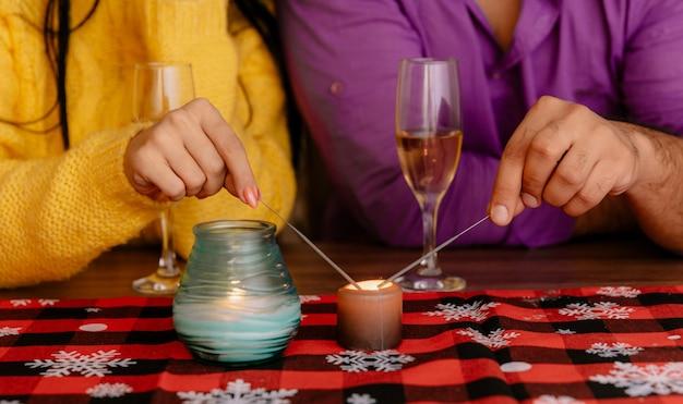 Photo Recadrée De Mains De Couple Mettant Le Feu De Cierges Magiques Assis à La Table Avec Des Verres De Champagne Photo gratuit