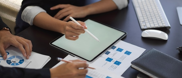 Photo Recadrée De Mains D'hommes D'affaires Travaillant Avec Tablette Et Graphique Sur La Table Photo Premium
