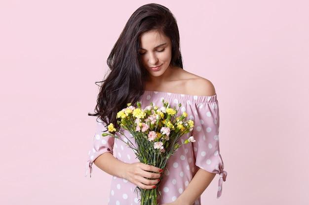 Photo D'un Séduisant Mannequin Femme Brune Avec Des Fleurs De Printemps Et Une Robe à Pois Photo gratuit